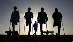 Four Palestinian friends, who were injured during conflicts, walk by the sea at Gaza's small fishing harbor.