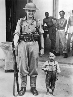 """Would-be sentry: The cute little feller with his hat at a jaunty angle is a friendly Chinese lad who decided to take up sentry duty in Hong Kong. He drew plenty of laughs as he stood his watch beside a British Navy sentry."" October 16, 1945."