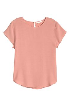 Blusa em crepe: Blusa de mangas curtas em tecido encrespado. Com abertura e botão na parte de trás do pescoço e base arredondada, ligeiramente mais comprida atrás.