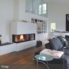 Einen warmen und gemütlichen Rückzugsort findet man in diesem modernen Wohnzimmer am Kamin mit angebauter Sitzbank. Die Wand dient praktischerweise als…