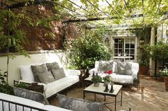 love this white and gray seating area protected with a vine-filled pergola