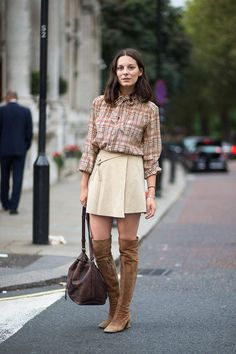 girl during fashion week wearing brown over the knee boots and plaid shirt and a beige skirt.