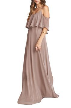 This flirty, floaty gown has a ruffled bodice overlay with drapey sides that can also be worn as fluttery sleeves. The elegantly simple A-line style flatters a variety of figures.