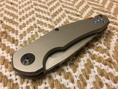 The ZT0220 is a collaboration between Zero Tolerance Knives and designer Jens Anso. Anso is a legend of a designer in the knife world and has been around since 1988. This is the first collaboration piece between the two. ( Product page) The 0220 is unmistakably Anso with its organic shape. This is a contrast to knives like the ZT0804CF. The handles are flat titanium slabs that are beadblasted and are chamfered for comfort . The build is similar to knives like the ZT0801 with black hardw...