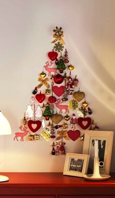 christmas tree shaped from ornaments on the wall