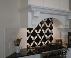 Bold Black and White Backsplash. Love the all-white relief tiles too.