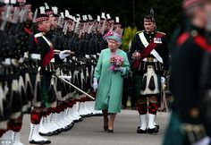 The Queen wore a pea green coat, a purple floral dress and a green and pink hat for the oc...