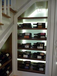 custom wine storage under stairs, backlit LED plexiglass rear panel with adjustable walnut shelving