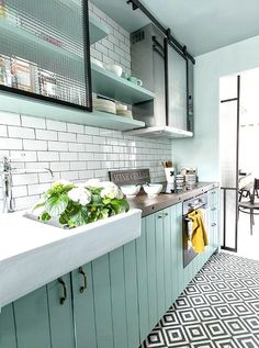 Kitchen with a farmhouse sink, subway tile, and blue cabinets in a Paris Apartment, via @brendak.