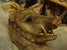 This pig head (maybe mask) is AMAZING!  The burlap suggest scarecrow, the pig head is a twist