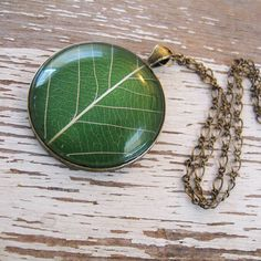 This grass-green leaf necklace is made from a real pressed leaf and is set in glass with antique brass