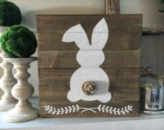 Think Spring! This adorable bunny hand-painted on a reclaimed wood plank sign makes for the perfect Easter and Spring décor. Rustic, simple, and cute!  Each sign is unique due to the natural variation of grain and knots in the wood. Approximate size is 12x12 and includes a natural jute rope for hanging. Each bunny has a handmade tail either of burlap or cotton. Choose whether you want a natural or white-washed wood for your sign. The natural wood sign will have a white bunny and burlap tail…