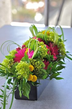 like these low long centerpieces.  lots of green and some pops of color