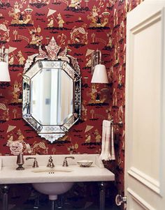 Shanghai Deco wallpaper in red from Clarence House adds a fanciful touch in the powder room. Swing-arm sconces with milk glass shades from Ann-Morris. Console sink from Smith's Country collection for Kallista.