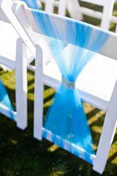 Reception chair back decorated with turquoise tulle and diamond wrap ribbon.