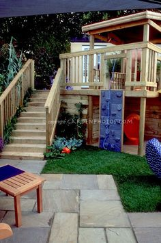 Great idea for a rock climbing wall for the kids to the deck. Love the IKEA swivel chair tucked under the deck for a playhouse.