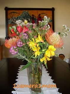 The protea is South Africa's national flower. These ones are called pin cushion proteas, because they look like pin cushions. They last a long time once cut and placed in water, but they are not fragrant. The bright yellow flowers and the almost red ones are called alstroemeria. They are very fragrant and beautiful too. http://1camera1mom.blogspot.com/2012/07/cut-flowers-11.html# #flowers
