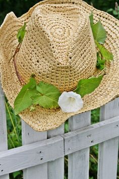d501f00bfa6 Straw hat with floral band hung on fencr