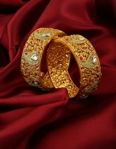 Creatively designed this pair of royal look bangles from Anuradha Art Jewellery is best pick for fashion conscious women. They are studded with kundan along with ruby stone and feature eye-pleasing intricate carving design on surface. These bangles are good in quality and skin-friendly as well. So buy now!