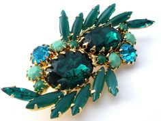 Vintage Costume Jewelry - This is a unique gold tone brooch with several shades of green rhinestons, accented with just a touch of blue. The large center stones have a pie crust setting with dog tooth