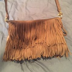 """TORY BURCH FRINGED CROSS BODY BAG Beautiful tan suede TB cross body bag. Gray for day night. Holds a lot of stuff and has an inside zip pocket and 2 separate small pockets. Zips on top. Zip pull missing from zipper but still closes. Suede fringe with leather bag. TB emblem on side in gold. May be missing a couple fringes but can not tell when using. Strap is 22"""" from top to bottom. Tory Burch Bags Crossbody Bags"""