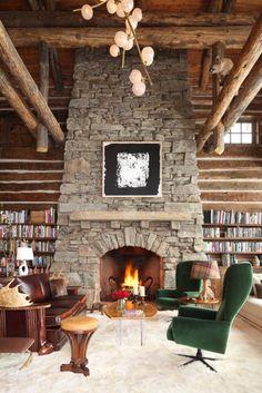 Great room with log siding, stone fireplace, Thomas Canada Molesworth-style sofa, English oyster-veneered coffee table, Czech modernist wingback chairs, hoof lamp, Biedermeier stool, Richard Serra drawing, and Jeff Zimmerman chandelier