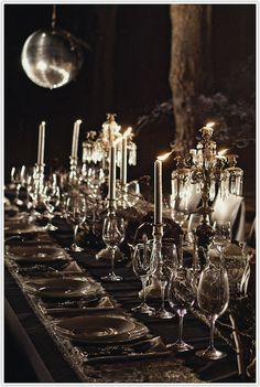 The strength of this table design comes from the black-on-black styling...illuminated by candlelight, a full moon and that fabulous seventies disco ball. A lacy tablecloth, gothic chandeliers and moss creeping across the entire table completes the mood.