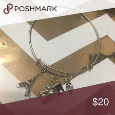 Handmade camera bangle bracelet 7.5 inch bangle bracelet with A camera charm, purple sparkle charm, and an Eiffel tower charm. Is adjustable to go over hand Jewelry Bracelets