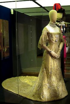 The coronation of King Haakon and Queen Maud took place on 22 June 1906 in Nidaros Cathedral in Trondhjem. Queen Maud's coronation dress, made of gold lamé in the princess style, has scalloped lace sleeves. A decorative pattern of flowers and ribbon bows was embroidered in gilt metal thread, gold-coloured sequins, artificial pearls and diamanté. The gown-making was a collaboration between fashion houses from Maud's new home Norway and her country of birth Britain.