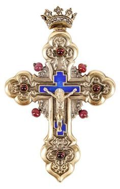 Faberge (Russian, founded 1842). Early 20th century gilt silver, diamond, ruby and guilloche enamel crucifix necklace pendant with diamond accented crown at top with pendant loop surmounting a trefoil lobed or budded cross (Apostles' Cross or Bottany Cross) with scrolled foliate motif amid four ruby cabochons and four ruby beads surrounding a blue guilloche enamel Russian Orthodox (also referred to as a Suppedaneum) cross with Christ with halo at center.