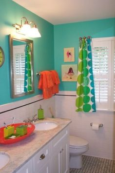 Great bright turquoise kids bathroom with orange accents