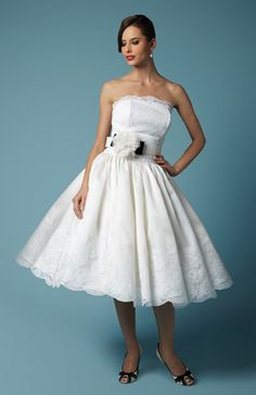 Joy - Strapless dropped waist bodice with lace trim, dress with gathered skirt and lace hem in satin faced silk organza, completed with blossom bow belt. - http://fancybridalny.com