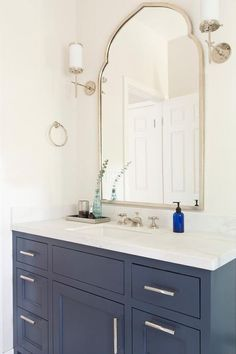 White and blue bathroom features a blue washstand adorned with long polished nickel pulls topped with white quartz placed below a silver leaf arched mirror, Uttermost Kenitra Arch Wall Mirror, illuminated by Hudson Valley Lighting Aberdeen Sconces.