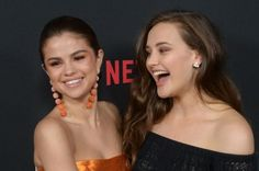 "Selena Gomez stunned in an orange Oscar de la Renta dress while attending the premiere of her Netflix series ""13 Reasons Why."""