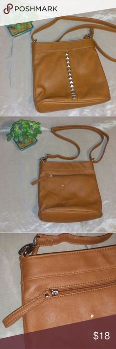 Carlos Santana shoulder bag Silver studs go down the front of this faux brown leather purse. There is a scratch on the back what you picture shows. One outside pocket and one inside zipper pocket and two inside open pockets. Pre-loved but still in good condition. 9x3x10 Carlos Santana Bags Crossbody Bags