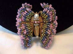 Spectacular and very Regal looking Miriam Haskell Butterfly Insect Brooch featuring layers of Glass Seed beads in beautiful colors of Blushing Pink, Sapphire Blue, and Olive Green all hand wired to an Antiqued Russian Gold Plate Ornate filigree back. Look closely and you will see the