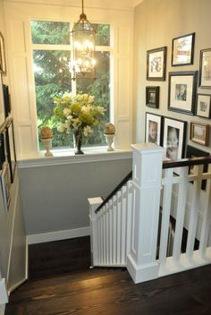 loving the dark floors contrasting with the white banister. fresh flowers, family photos.
