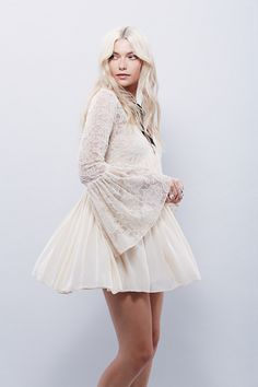 With Love Dress | Super cute mini dress with a sheer mesh bodice featuring floral embroidery. V-Neckline with a dramatic flare bell sleeve and buttondown closure detailing. Crinkly skirt in an effortless, swingy fit with pleating. Lined with a removable slip.