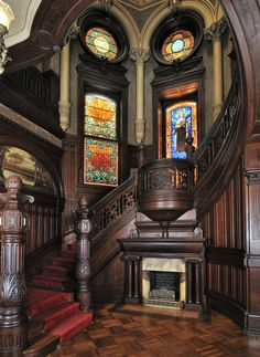 High Victorian Entry with firplace and Grand Staircase: Bishop's Palace. Galveston, TX. Dark wood tones, ecclesiastical-like details on columns, stairway, and  ethereal stained glass windows.