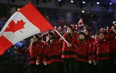 Hayley Wickenheiser of Canada carries her country flag as they arrive during the opening ceremony of the 2014 Winter Olympics in Sochi, Russ...