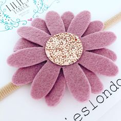 ABOUT ............ A pretty, dusky pink, daisy headband. This pretty flower headband is perfect for children and babies. Our nylon headbands are so soft, so fit all ages from newborn to adult. The flower is made using 100% wool felt and high quality, non shedding, glitter fabric.