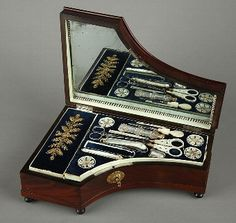 mahogany sewing casket simulating a piano, with a hidden music box. Inside the casket a set of beautiful mother of pearl instruments on blue velvet.