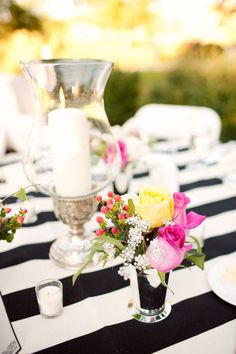 Silver cups filled with bright pops of color add the perfect festive touch to the bold black & white striped linens.
