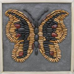 Butterfly - Bruce Bay gold-coloured stones, Ngakawau blacks and reds with polished quartz. Background is cementitious grout poured on to wet sand.