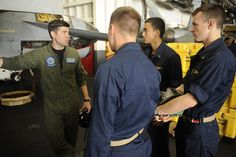 "GULF OF OMAN (June 29, 2013) – Lt. Billy Gum, assigned to the ""Blue Diamonds"" of Strike Fighter Squadron (VFA) 146, speaks with midshipmen during a tour of the hangar bay aboard the aircraft carrier USS Nimitz (CVN 68). Nimitz Strike Group is deployed to the U.S. 5th Fleet area of responsibility conducting maritime security operations, theater security cooperation efforts and support missions for Operation Enduring Freedom."