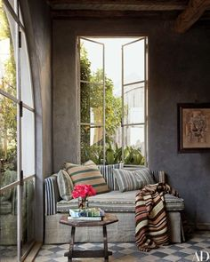 A daybed covered in stylishly mismatched stripes is tucked into a corner of the library of a Malibu, California, home by Richard Shapiro; the table is 15th-century Italian, and the painting is by Shapiro.