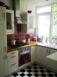 layout. red tiles are great with the wooden bench tops. Also good how the tiles behind the stove go right up to the hood.