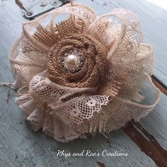 A handmade burlap rosette fabric flower surrounded by layers of frayed tan and ivory burlap fabric and vintage ivory lace trim with an ivory pearl rhinestone button. Perfect for any kind of embellishing! ***Custom Made for you similar to the one shown here. Measures approximately 4.5 x 4.5   *** PRODUCTION TIME for Custom Made orders is approximately 1-2 weeks or 5-10 days depending on my current turnaround and any materials I may need to order to create your flowers. ***If you have any…
