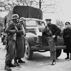 Nazi Military Police, Feldgendarmerie, guard a Canadian Food Truck after the end of war in Europe. Despite formal surrender, many German units physically retained their arms and the German Military Police even continued to keep order with Allies for more than a year. Dated sometime in 1945