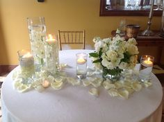 Wedding centerpiece set up of diamond banded staggered height cylinders with submerged white dendrobium orchids topped with floating candles.  White stock, white roses, white cushion pins, white lisianthus, and white hydrangea in glass cylinder surrounded with rose petals, votive candles and cylinders with floating candles.  Doristhefloristt@aol.com